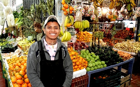 mexico yucatn peninsula quintana roo cancun mercado 23 hispanic man young adult smiling apron local produce fruit market business vendor vegetables tangerines bananas squash potatoes display crates for sale shopp