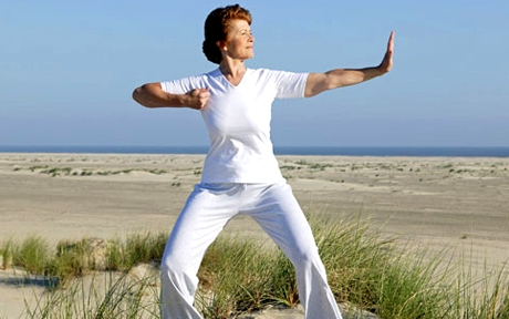 photolibrary rm photo of woman doing tai chi on beach
